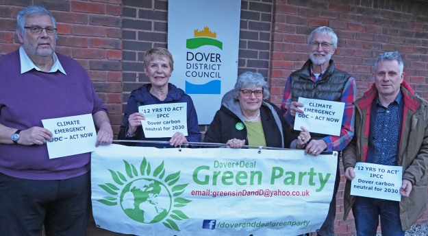 Green party members holding up signs stating '12 years to act', 'Climate emergency', 'Dover Carbon Neutral for 2030', 'Act Now'.
