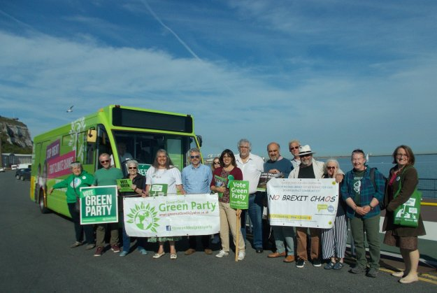 Local Greens stand with banners outside the electric campaign bus on Dover seafront